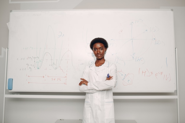 African american woman stand at whiteboard with formula and graph chart