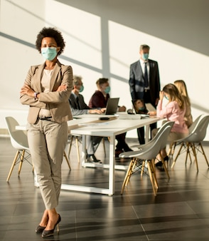 Афро-американских женщина, стоя в офисе перед своей командой и носить маску для защиты от вируса короны
