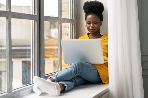 Афро-американская студентка с афро-прической в желтом кардигане сидит на подоконнике, работает удаленно на ноутбуке, учится с помощью онлайн-курса. самообразование, подготовка к экзамену.
