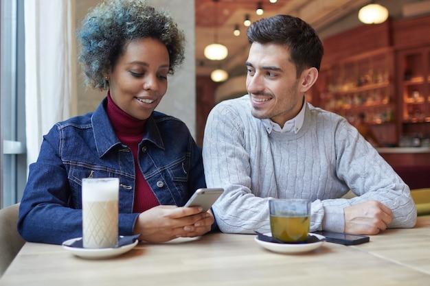 彼女のボーイフレンドが彼女を見つめている間、カフェで彼女の電話でウェブをサーフィンしているアフリカ系アメリカ人の女性