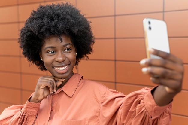 スマートフォンで自分撮りをしているアフリカ系アメリカ人の女性