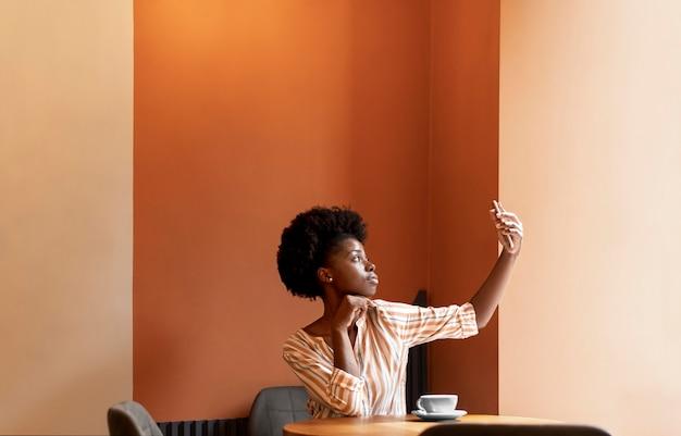 Donna afroamericana che si fa un selfie con il suo smartphone