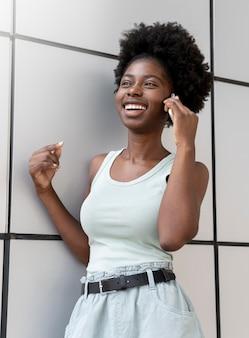 彼女のスマートフォンで誰かと話しているアフリカ系アメリカ人の女性