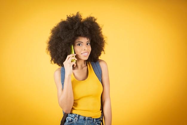 アフリカ系アメリカ人の女性がスマートフォンで話し、新しいアプリのダウンロードを推奨し、新しいゲームを発表し、