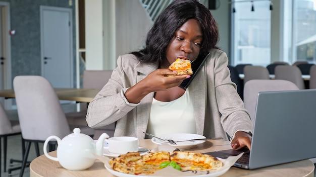Афро-американская женщина разговаривает по телефону, ест пиццу в кафе