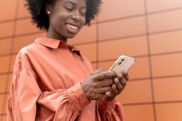 Donna afroamericana che manda un sms a qualcuno sul suo smartphone