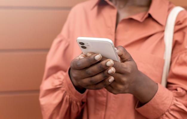 Афро-американская женщина пишет кому-то на своем смартфоне