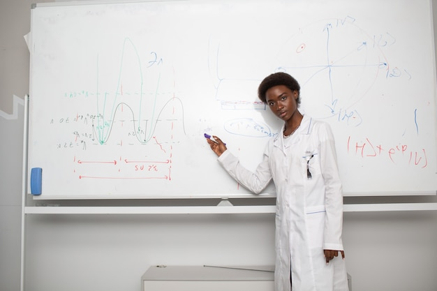 African american woman univercity student writing on blackboard with marker