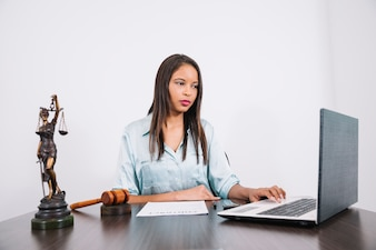 African American woman using laptop at table with document and figure