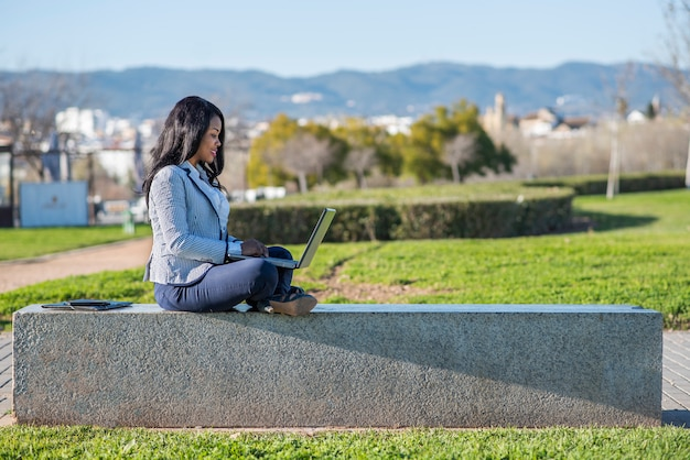 African-american woman using a laptop in an outdoor park