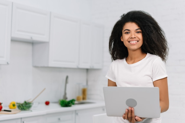 African american woman using laptop, shopping online from home. smiling hipster girl ordering food on website