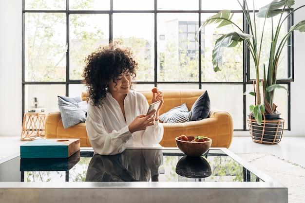 Афро-американская женщина с помощью мобильного телефона в квартире-лофте технологическая концепция домашняя концепция
