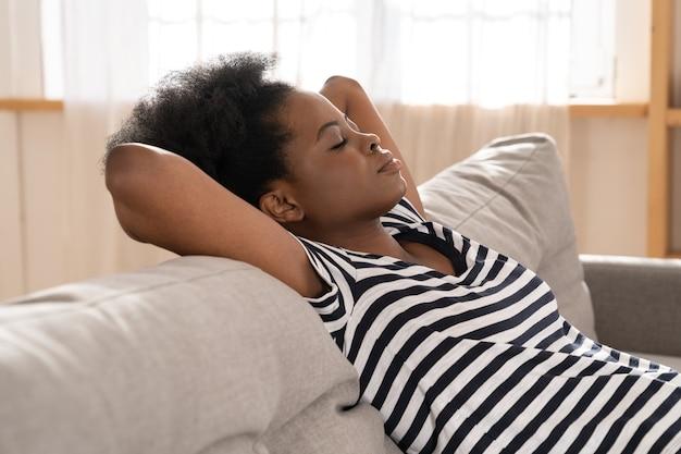 아프리카 계 미국인 여자는 집에서 머리 아래 팔을 소파에 자고 벗겨진 된 티셔츠를 착용합니다. 쉬다.