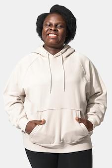 편안한 베이지 색 까마귀를 입고 아프리카 계 미국인 여자
