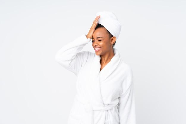 African american woman wearing bathrobe over white wall