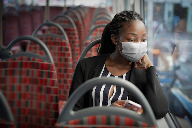 새로운 정상에서 대중 교통으로 여행하는 동안 버스에 마스크를 쓰고 아프리카 계 미국인 여자