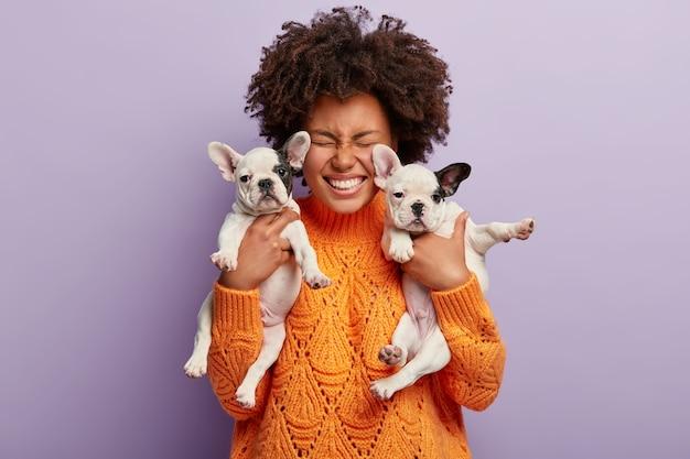 子犬を保持しているオレンジ色のセーターを着ているアフリカ系アメリカ人の女性