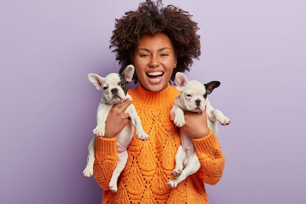 Donna afro-americana che indossa i cuccioli di azienda maglione arancione