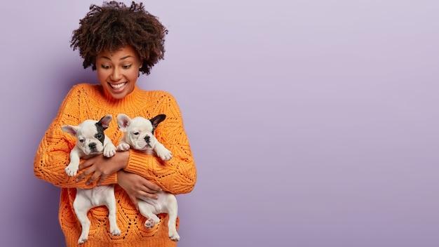 Афро-американская женщина в оранжевом свитере с щенками