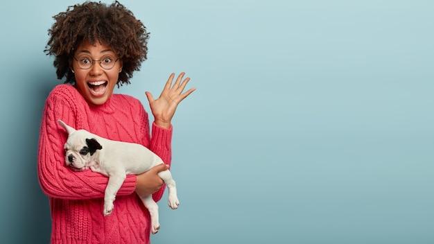 Donna afro-americana che indossa un maglione rosa tenendo il cane