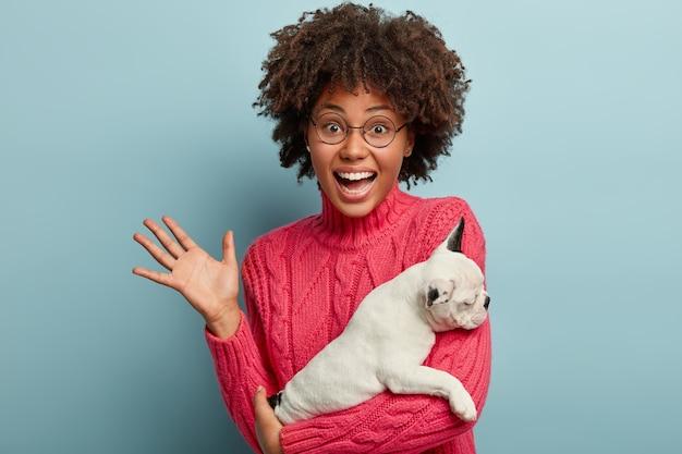 개를 들고 분홍색 스웨터를 입고 아프리카 계 미국인 여자