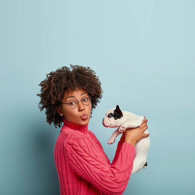 犬を保持しているピンクのセーターを着ているアフリカ系アメリカ人の女性