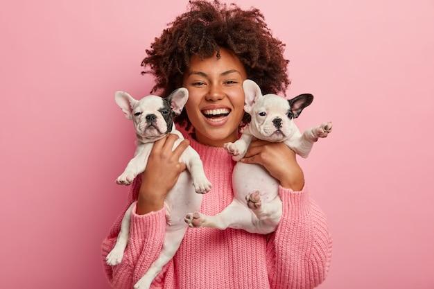 子犬を保持しているピンクのセーターを着ているアフリカ系アメリカ人の女性
