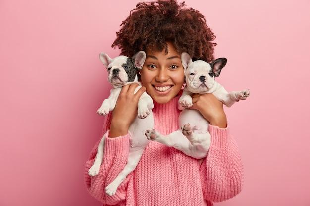 Donna afro-americana che indossa un maglione rosa che tiene i cuccioli