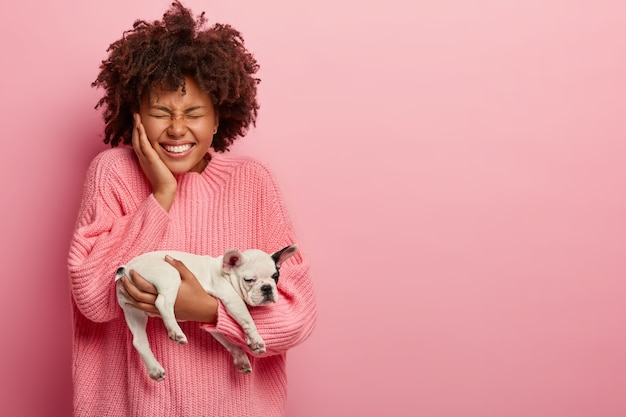 강아지를 들고 분홍색 스웨터를 입고 아프리카 계 미국인 여자