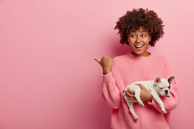 Donna afro-americana che indossa un maglione rosa che tiene cucciolo