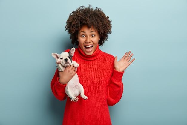 Donna afro-americana che indossa un maglione rosso tenendo il cane