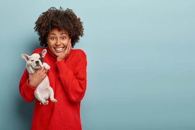 犬を保持している赤いセーターを着ているアフリカ系アメリカ人の女性