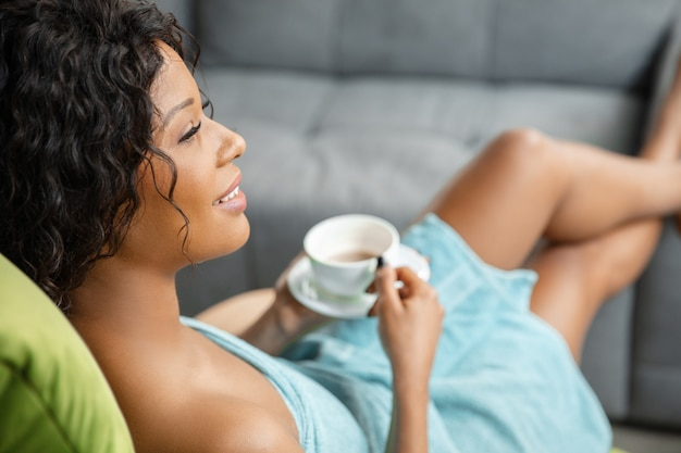 自宅で毎日のスキンケアルーチンをしているタオルを身に着けているアフリカ系アメリカ人の女性。
