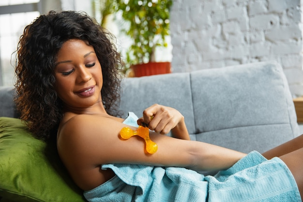 Donna afroamericana che indossa un asciugamano facendo la sua routine quotidiana di cura della pelle a casa.