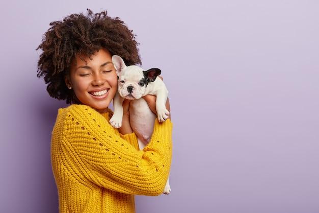 Donna afro-americana che indossa un maglione giallo che tiene cucciolo