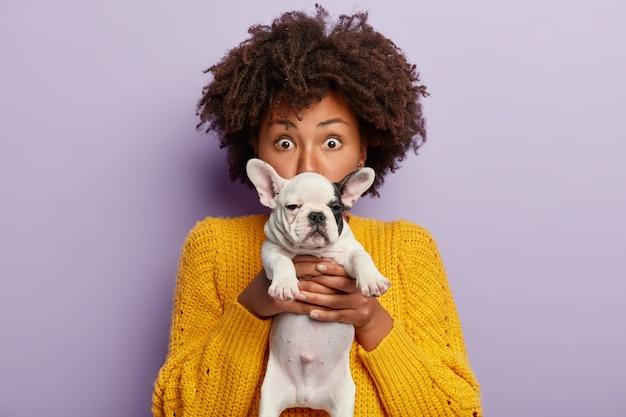 강아지를 들고 노란색 스웨터를 입고 아프리카 계 미국인 여자