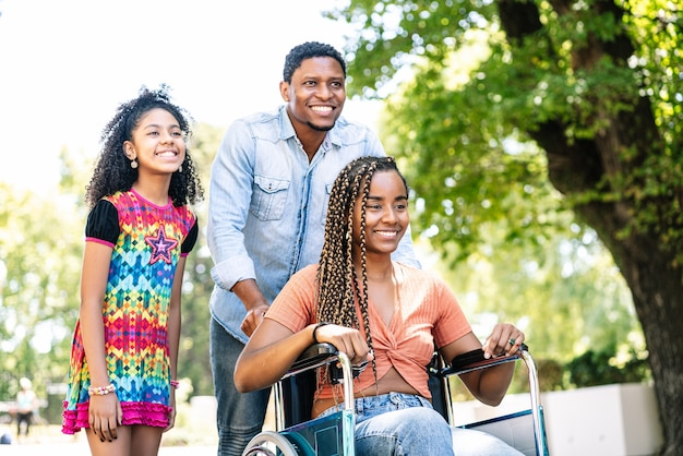 An african american woman in a wheelchair enjoying a walk outdoors with her daughter and husband.