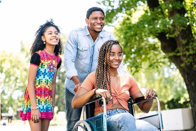 Una donna afroamericana su una sedia a rotelle si gode una passeggiata all'aperto con la figlia e il marito.