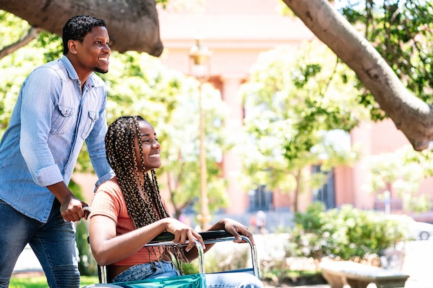 An african american woman in a wheelchair enjoying a walk at the park with her boyfriend.
