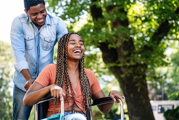 An african american woman in a wheelchair enjoying a walk with her boyfriend.