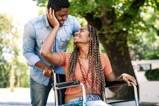 An african american woman in a wheelchair looking at her boyfriend and touching his face while enjoying a walk together.