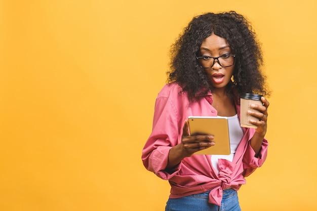 テイクアウトのコーヒーやお茶を飲んでよそ見アフロ髪型のアフリカ系アメリカ人の女性