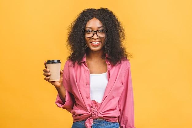 Афро-американская женщина с афро-прической смотрит в сторону, пьет кофе на вынос из бумажного стаканчика