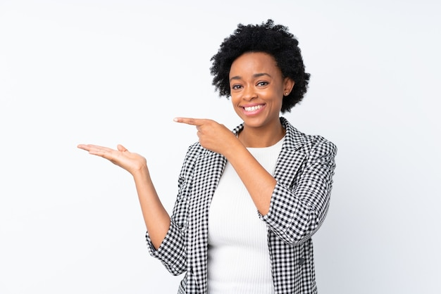 African american woman with blazer on isolated white holding copyspace imaginary on the palm to insert an ad