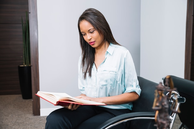 African american woman with book sitting on armchair in office