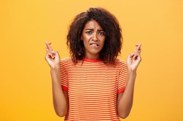 Афроамериканка с кудрявой прической тревожно кусает нижнюю губу и скрещивает пальцы