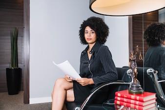 アフリカ系アメリカ人女性のオフィスの肘掛け椅子に座って書類