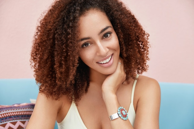 African american woman with frizzy dark hair, has broad smile, being satisfied to spend summer holidays in resort country
