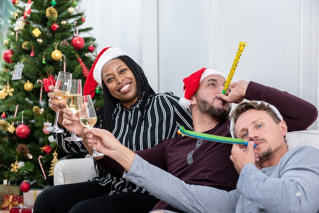 African american woman with group of friends celebrating christmas at home