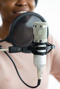 녹음 스튜디오에서 팟캐스트를 녹음하는 헤드폰과 마이크를 가진 아프리카계 미국인 여성